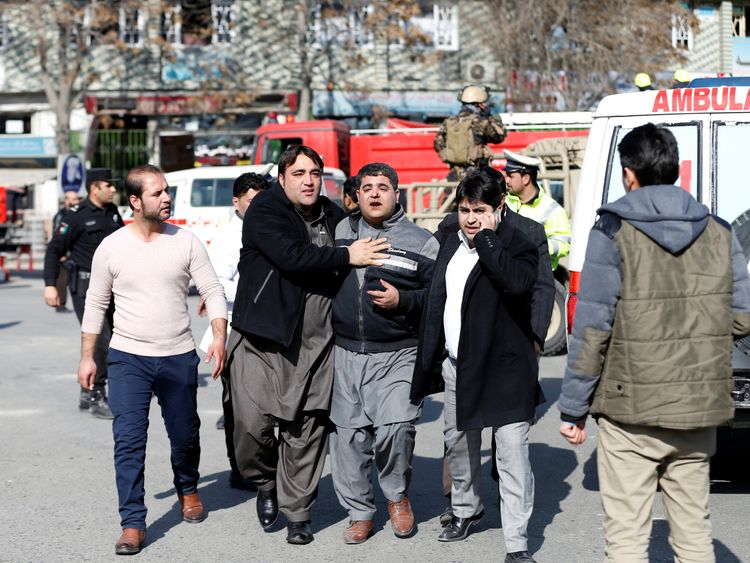 People assist an injured man after a blast in Kabul, Afghanistan January 27, 2018