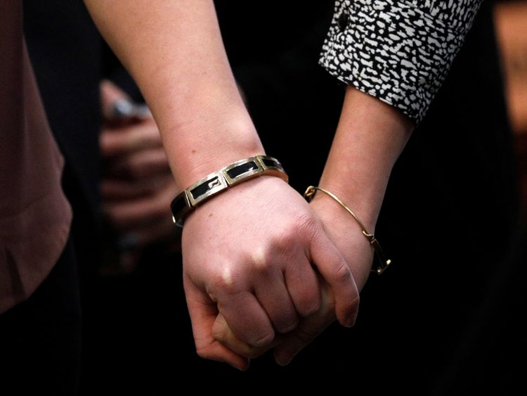 Victims and former gymnasts Maddie (L) and Kara Johnson hold hands as they speak at the sentencing hearing