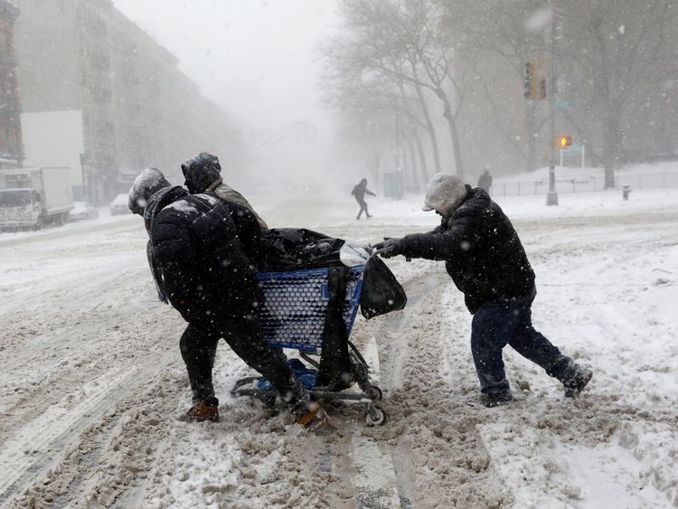 A group of men struggle against the storm as they cross 125th street in upper Manhattan, New York