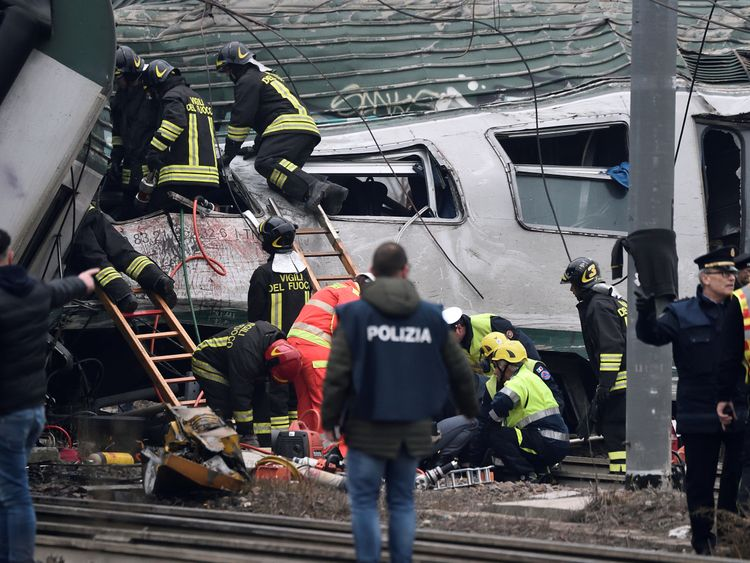 Fire fighters and police officers work around derailed trains in Pioltello, on the outskirts of Milan, Italy, January 25, 2018