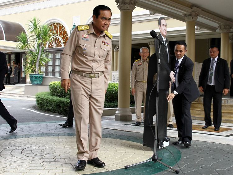 Thailand's Prime Minster Prayuth Chan-ocha speaks to reporters next to a cardboard cut-out of himself