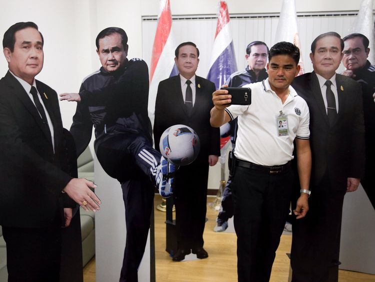A journalist selfies with cardboard cut-outs of Thailand's Prime Minister Prayuth Chan-ocha
