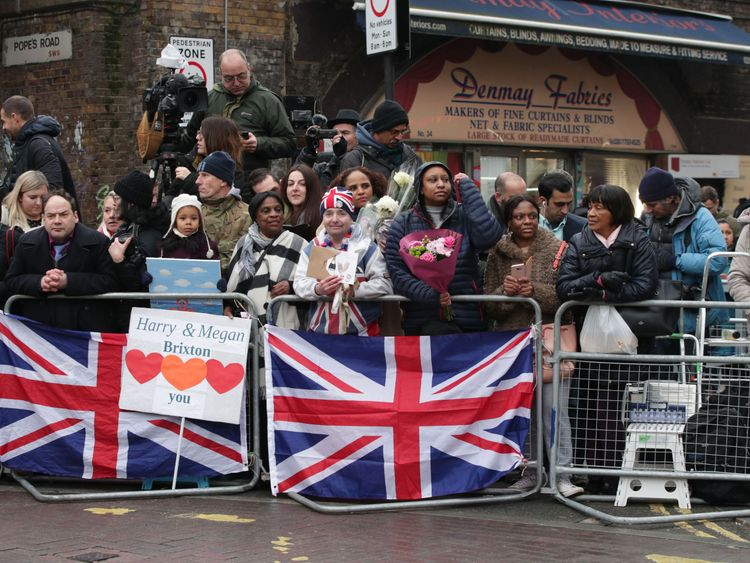 People wait for the arrival of Prince Harry and Meghan Markleat Reprezent FM, in Brixton, south London