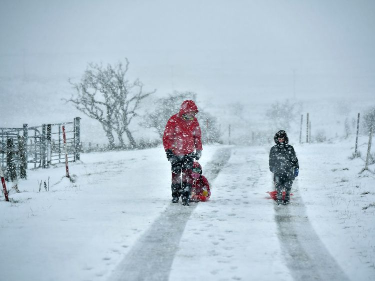A father and his children make their way through the snow in Belfast