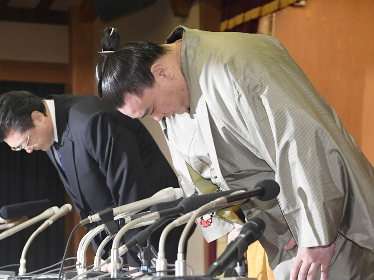 Harumafuji bows in apology with his stable master during his retirement conference. Pic: Kyodo/via REUTERS