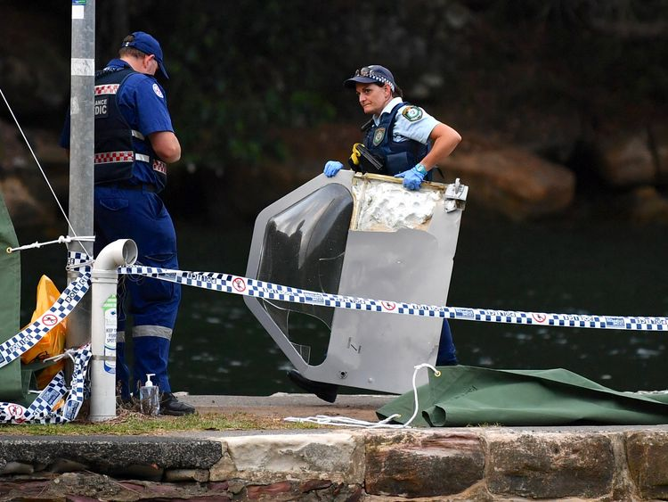An Australian policewoman holds a piece of debris from a seaplane that crashed on Sunday killing six