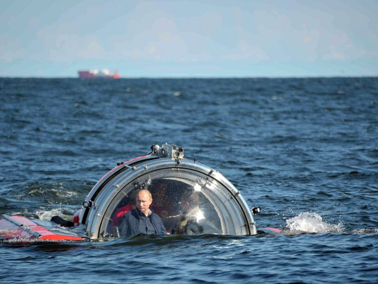 "Putin (L) is seen through the glass of C-Explorer 5 submersible after a dive to see the remains of the naval frigate ""Oleg"" in 2013"