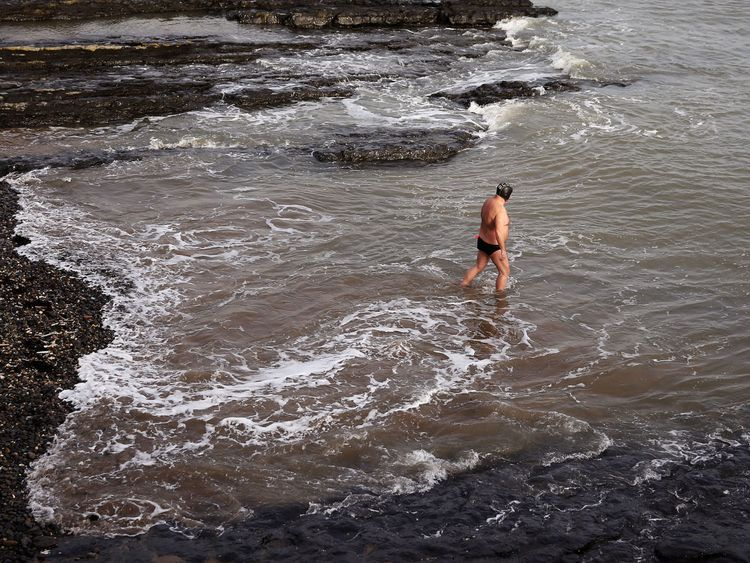 A man goes for a swim in the Irish sea at Low Rock in Portmarnock, Dublin