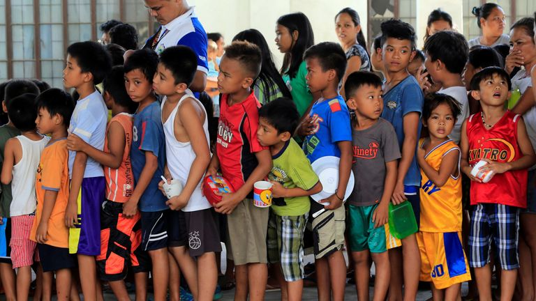 Children line up for snacks at an evacuation centre