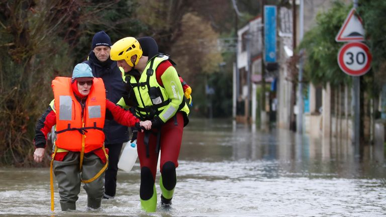Fire brigade divers help a woman after she returned home to feed her animals