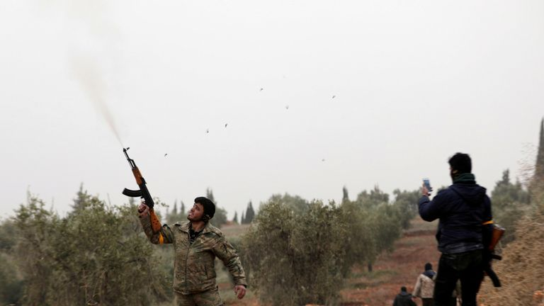 A free Syrian Army fighter shoots his gun near Mount Barsaya, northeast of Afrin