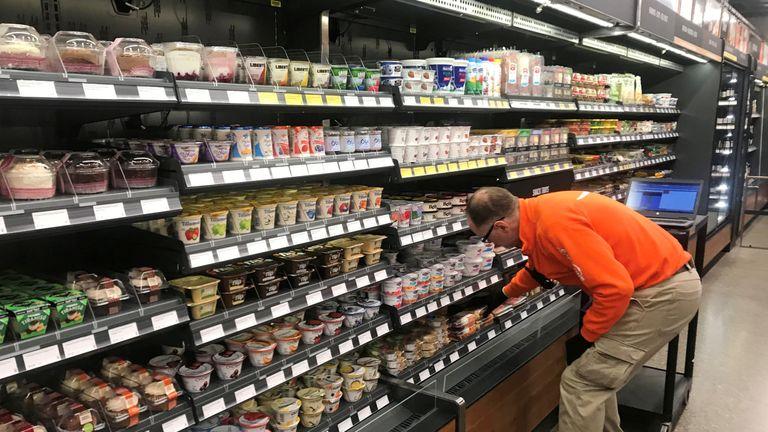A man restocks the shelves in the Amazon Go supermarket