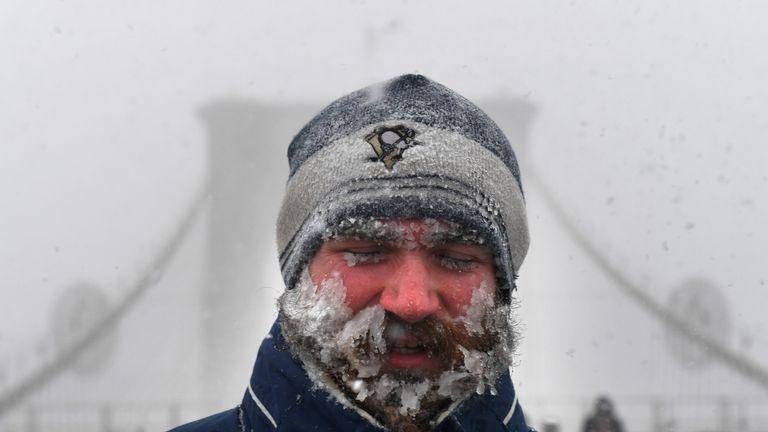 A pedestrian walks through blinding snow across the Brooklyn Bridge during Storm Grayson in New York City, U.S., January 4, 2018