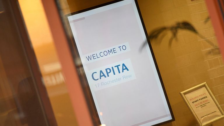 An illuminated sign is seen in Capita offices in London