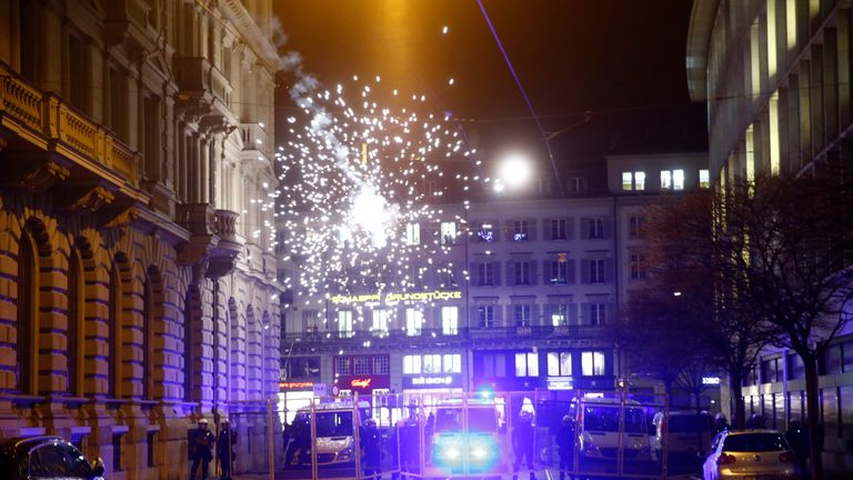 Fireworks explode over riot police during an anti-U.S. President Donald Trump demonstration in Zurich