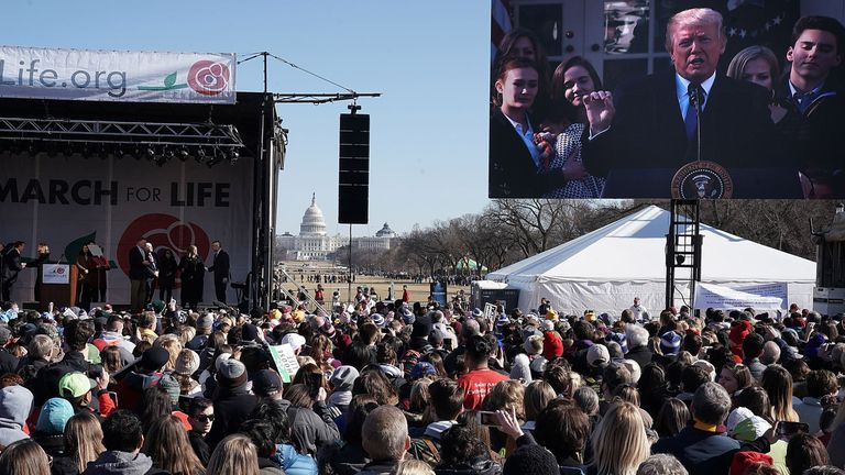 Pro-life activists watch Donald Trump addressing an anti-abortion rally prior to the 2018 March for Life