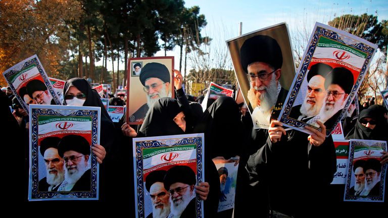 Counter-protesters holding posters of Ayatollah Ali Khamenei and Ayatollah Ruhollah Khomeini