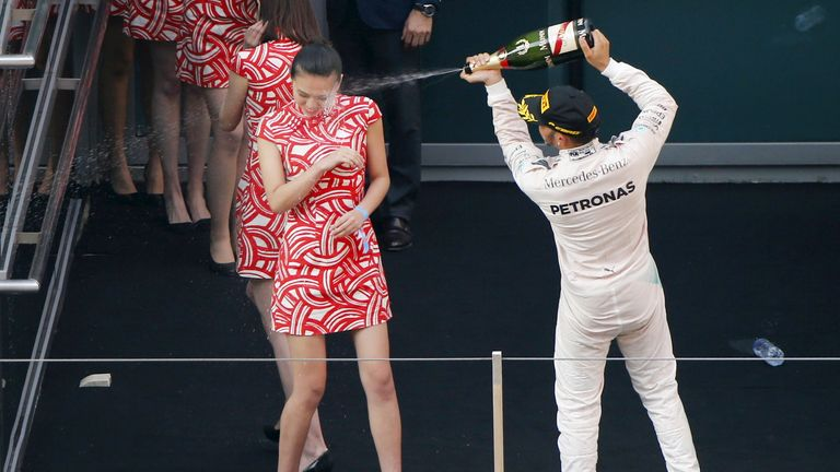 Lewis Hamilton sprays champagne at a grid girl as he celebrates his victory after the Chinese F1 Grand Prix in April 2015