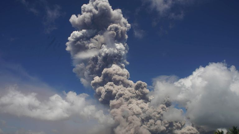 A giant mushroom-shaped cloud rises into the air from the Mayon volcano