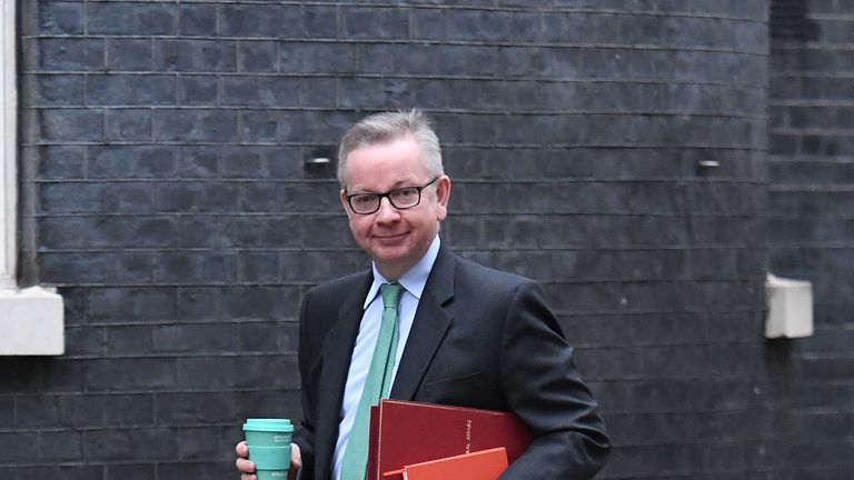 Environment Secretary Michael Gove holds a reusable coffee cup as he arrives in Downing Street.