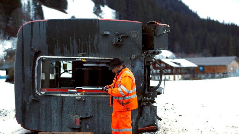 A Montreux Oberland Bernois worker inspects the derailed train carriage