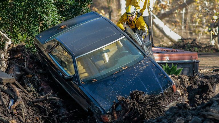 Rescue workers search a car after a mudslide in Montecito