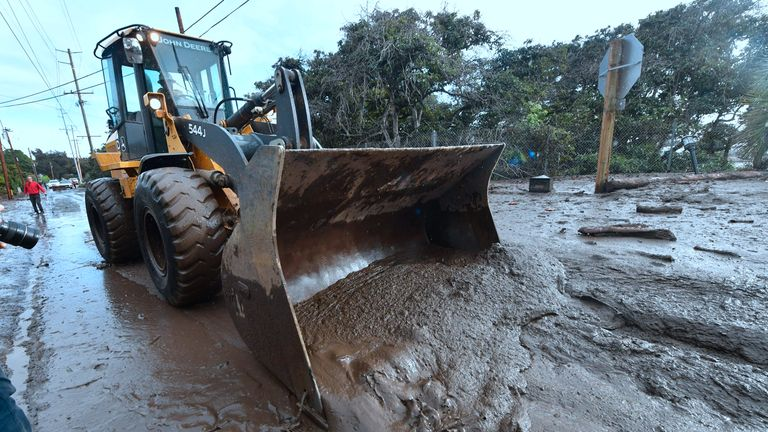 A bulldozer clears mud off the road near a flooded section of US 101 freeway in Montecito, California