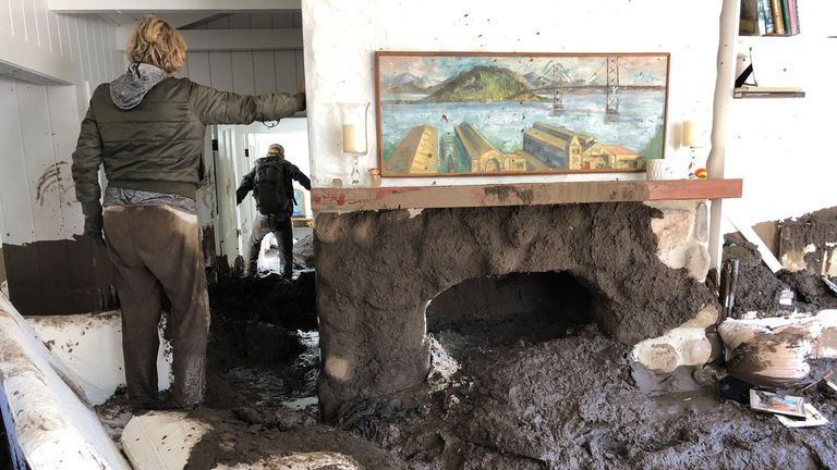 Family members inspect the inside of a home covered in mud