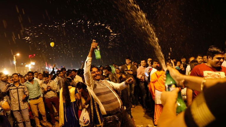People dance during the New Year's celebrations on a beach in Mumbai, India, January 1, 2018