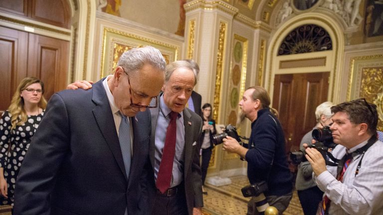 Senate Minority Leader Chuck Schumer (L) and Senator Tom Carper (R) walk out of a Democratic Caucus meeting at the US Capitol