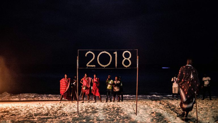 People wait for a moment to light a sign that reads 2018 during the New Year's Eve celebration on Nungwi Beach in Zanzibar, Tanzania, on December 31, 2017. / AFP PHOTO / GULSHAN KHAN (Photo credit should read GULSHAN KHAN/AFP/Getty Images)