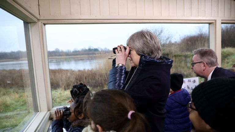 Theresa May watches birds from inside a bird hide with school children at the London Wetland Centre in Barnes