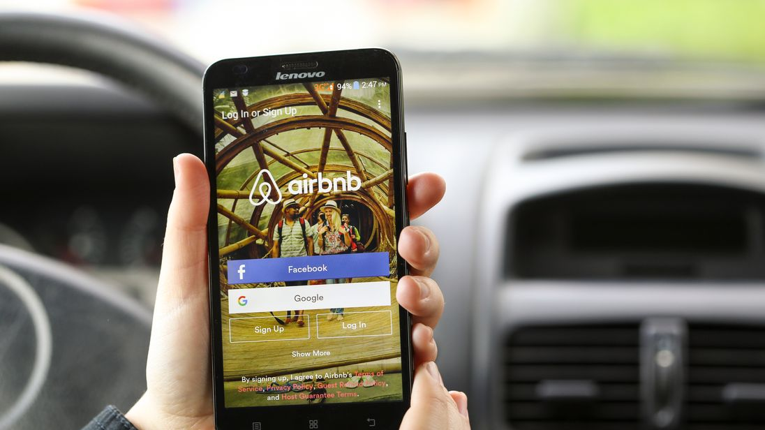 Close-up of an unrecognizable woman using the Airbnb App on her Lenovo A916 Android smartphone in a car. Login screen with Facebook and Google sign up options. Airbnb is a service for people to list, find, and rent lodging. It currently has over 1,500,000 listings in 34,000 cities and 190 countries.