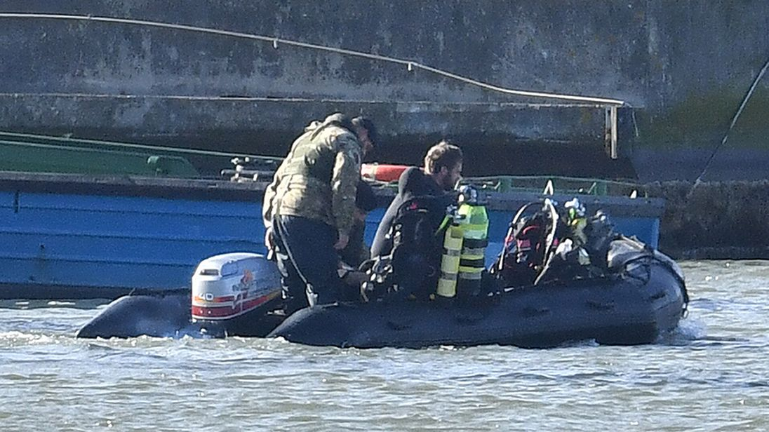 Royal Navy bomb disposal divers on a boat in King V George Dock close to London City Airport