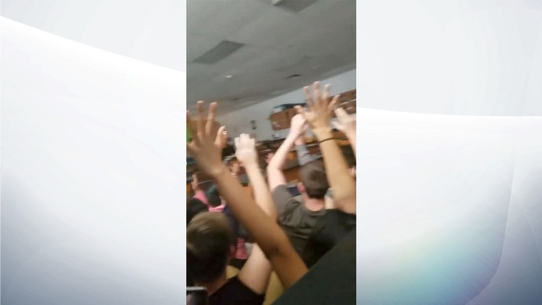 Students raise their hands as armed police enter a classroom. Pic: Alexander Ball