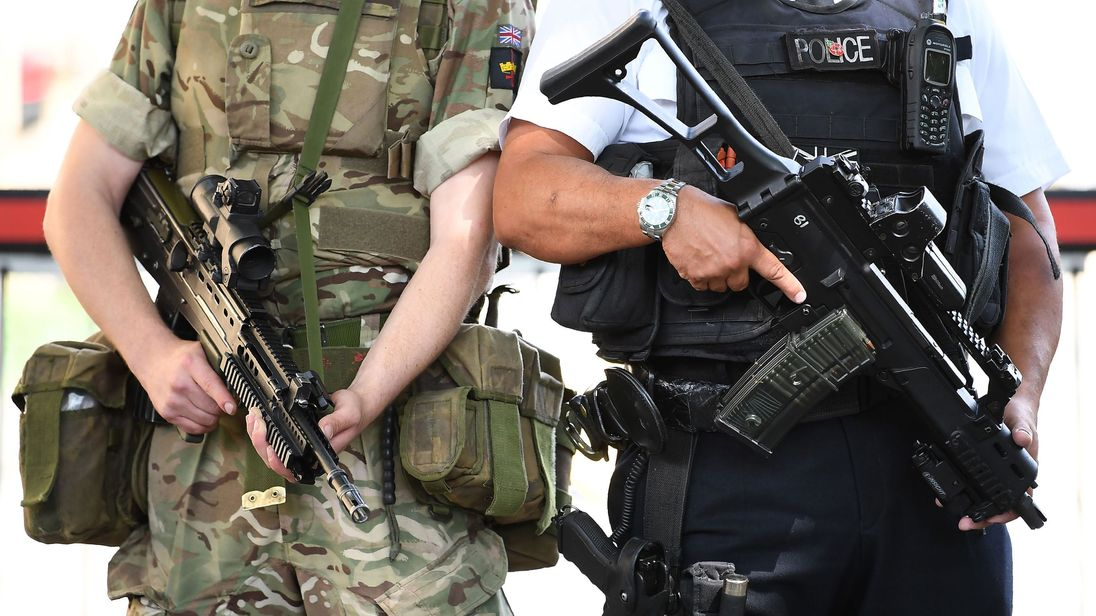 A British Army soldier patrols with an armed police officer near the Houses of Parliament in central London on May 24, 2017