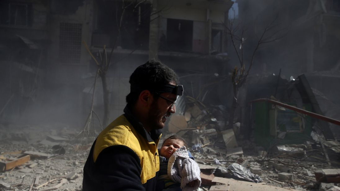 A baby is carried away from the remains of a bombed out building