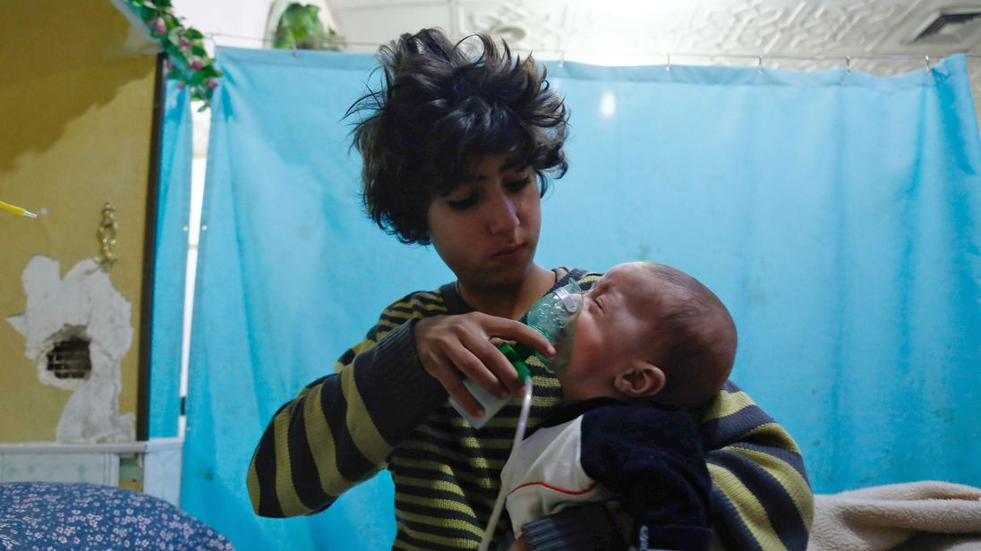 A Syrian boy holds an oxygen mask over the face of an infant following a reported gas attack on the rebel-held besieged town of Douma