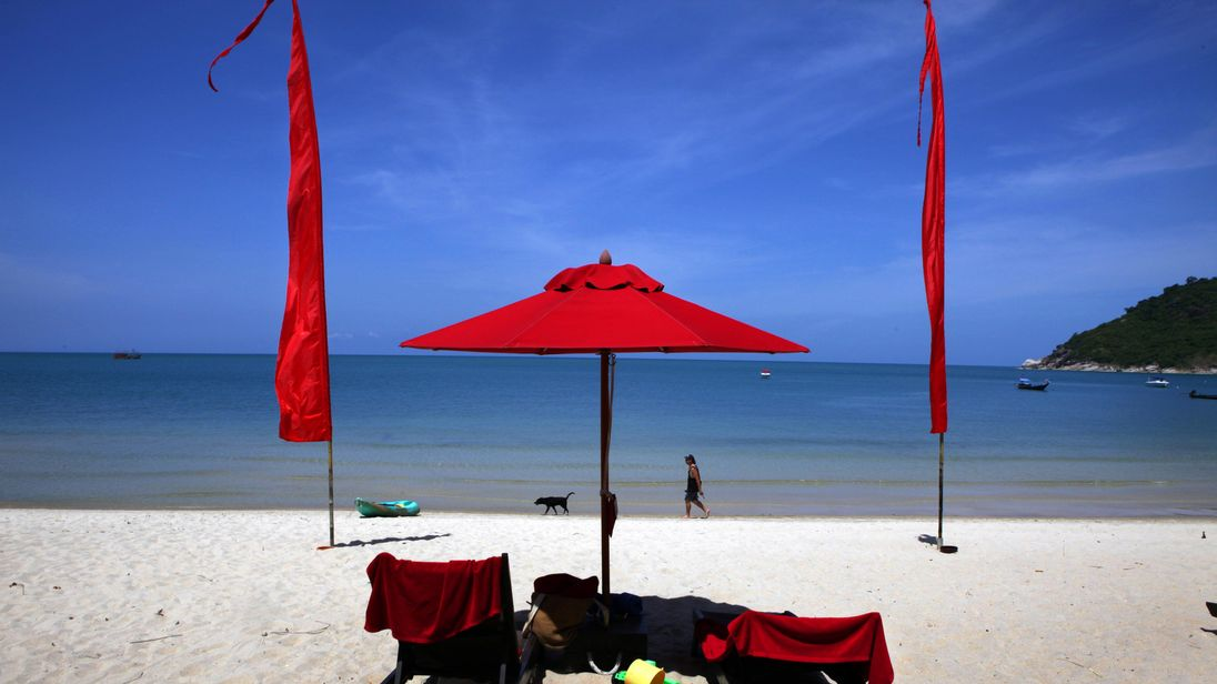 KOH PHANGAN THAILAND - JUNE 18: A white sand beach decorated by red umbrellas at the Anantara Rasananda resort June 18, 2012 on the island of Koh Phangan off the coast of Koh Samui . Thailand's official tourism body, the Tourism Authority of Thailand (TAT) has set itself the ambitious target of attracting more than 20 million tourists in 2012. According to TAT, In April, Thailand welcomed 1,659,021 international tourists which is a slight increase of 6.87% over the same in 2011. (Photo by Paula