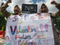 Girls from a local boarding school shout during an anti-Valentine's Day rally