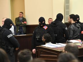 Prime suspect in the November 2015 Paris attacks Salah Abdeslam (L) sits beside his alleged accomplice Sofiane Ayari (R) as they are surrounded by Belgian special police officers