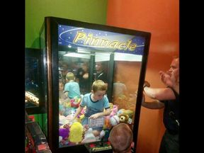 Little boy gets stuck in arcade claw machine trying to get a toy - aptn