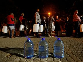 People queue to collect water from a spring in the Newlands suburb as fears over the city's water crisis grow in Cape Town, South Africa, January 25, 2018