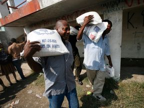 In this handout image provided by the United Nations Stabilization Mission in Haiti (MINUSTAH), Haitians carry food distributed by UN personnel outside a stadium, which has become an IDP camp, January 20, 2010 in Leogane, Haiti