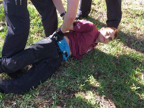 Police detain Nikolas Cruz at the scene of the Parkland school shooting