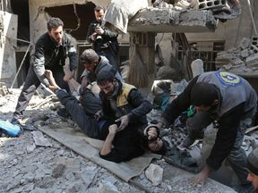 Members of a Syrian civil defence team rescue a man following an airstrike in Hamouria, eastern Ghouta