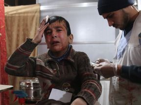 Ghaith, a wounded 12-year-old Syrian boy, cries as he receives treatment at a make-shift hospital in Kafr Batna and waits for news of his mother in the operating room