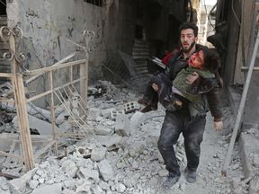 A Syrian man rescues a child after an air strike in eastern Ghouta