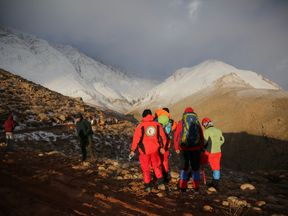 Members of emergency and rescue team search for the plane that crashed in a mountainous area of central Iran, February 19, 2018