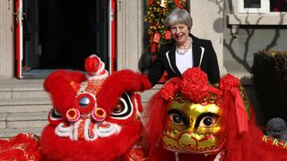 Prime Minister Theresa May stands with Dragons outside the British Embassy in Beijing on February 1, 2018 in Beijing, China